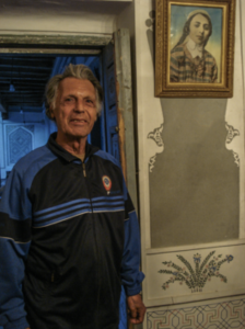 Mubinjon Tadzhiev, 2008, in a tracksuit of the national sports team of the Uzbek Soviet Socialist Republic, above him a colored photograph of his mother (Photo by Stefan Applis)